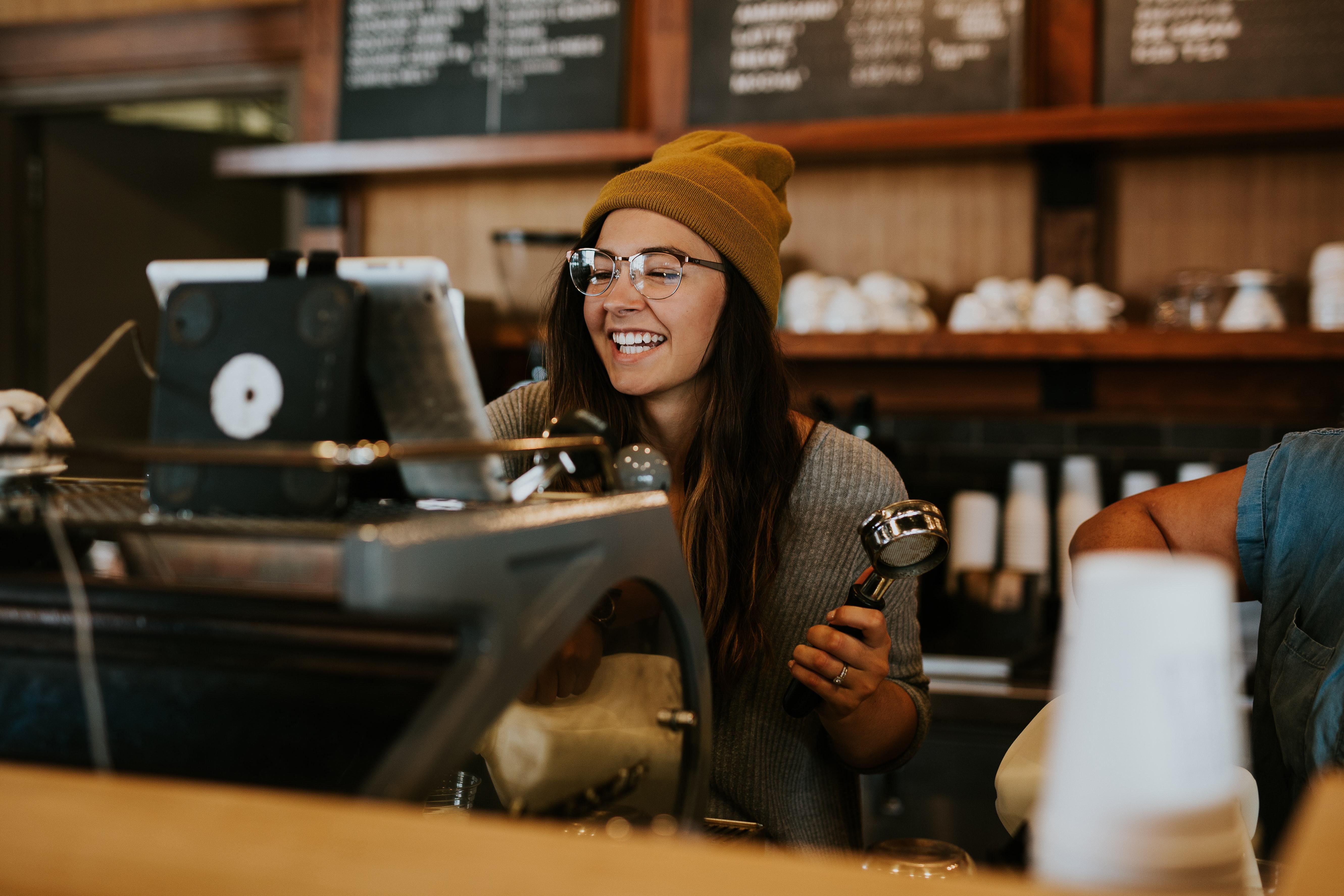 smiling barista working at espresso machine